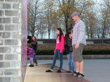 John Collins, 33, of Austin, Texas, wears shorts while he visits the glowing Crown Fountain Monday with his wife's nieces, who live in Tinley Park.