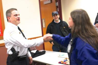 "New Shakespeare District Cmdr. Francis ""Frank"" Valadez greets Kerri Stojak, a staffer in Ald. Scott Waguespack's office at the end of Wednesday's CAPS meeting. Waguespack  (32nd) is wearing a cap."