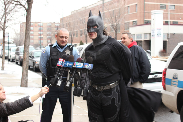 <p>Batman, portrayed by Bobby Kordelewski, talks Christmas morning about surprising the 4- and 7-year-old survivors of a deadly fire.</p>