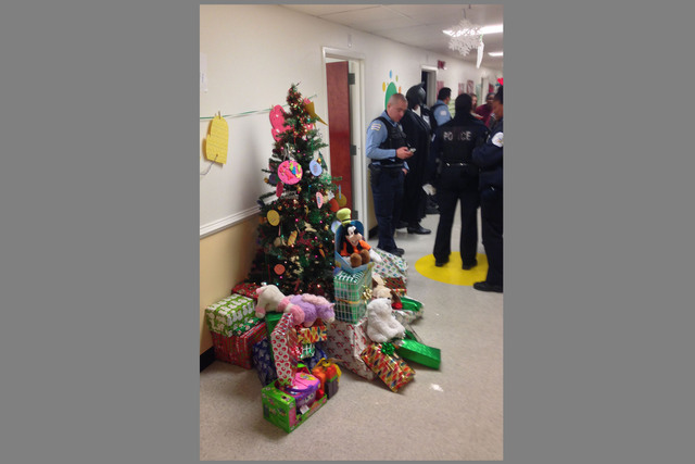 <p>Police gather in the hall of a DCFS facility on Christmas morning&nbsp; to surprise the 4- and 7-year-old survivors of a deadly Englewood fire. Donated gifts for the boys are piled near a Christmas tree.</p>