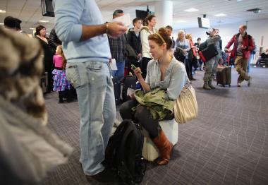 Passengers wait at the airport amid flight delays and cancellations.