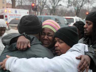 Gwendolyn Moore (center) is comforted by a friend at the corner of Ashland and Garfield, where she said her son, Jamaal More, 23, was shot dead by police.