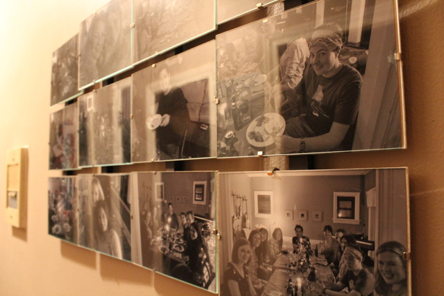 <p>Emily Hurd, who hosts a monthly supper club at her Edgewater apartment, keeps photos of past supper clubs on the wall of her place.</p>