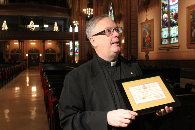 <p>Rev. Boland holds up the certificate from the Vatican that declares the authenticity of Holy Family&#39;s recently acquired relics.The church received the relics as a gift for its 155th anniversary.</p>