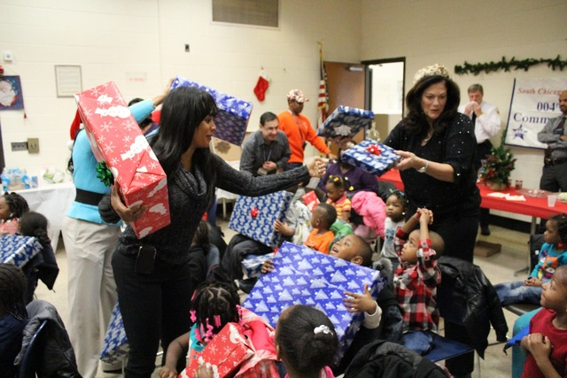 <p>Ald. Sandi Jackson (7th) helps hand out presents to preschoolers visiting Santa at the South Chicago District police station.</p>