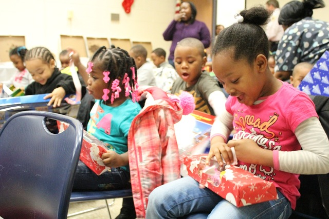 <p>Preschoolers from the Ada S. McKinley Trumbull Park Head Start program open presents from their local police district.</p>