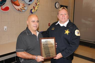 Businessman Suhail Fakhouri receives a plaque Tuesday from Englewood District Cmdr. Leo Schmitz as appreciation for sponsoring a toy giveaway for the last five years.