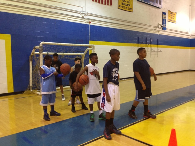 <p>Young basketball players listen to instructions from Ronnie Fields at Farragut. About 20 players, ages 8-18, attend the weekly workouts at the school.</p>