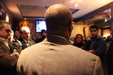 Ald. Walter Burnett (27th) speaks to a packed house at Tuesday night's community meeting at 9 Muses. Burnett called the meeting to address recent area shootings.