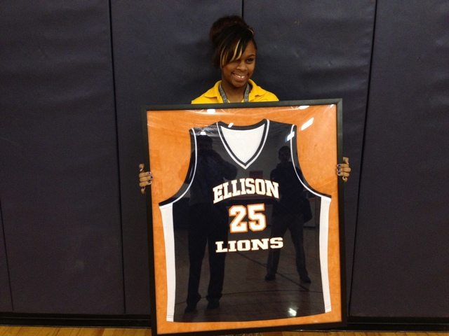 <p>CICS-Ellison senior guard Ariel Green holds the game-worn jersey of her brother, Estavion Green, who was fatally shot in 2011. Estavion&#39;s jersey hangs in the Ellison gym.</p>
