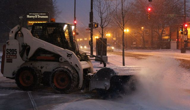 <p>A Bobcat blows away Friday morning&#39;s snow on West Wilson Avenue in Uptown.</p>