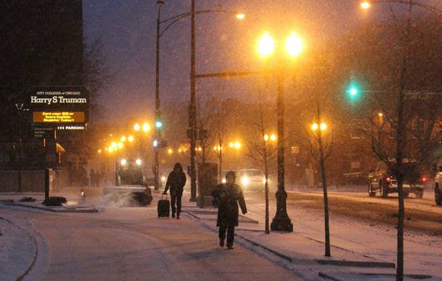 <p>Commuters make their way through Friday morning&#39;s snow near the Wilson Red Line stop in Uptown.</p>