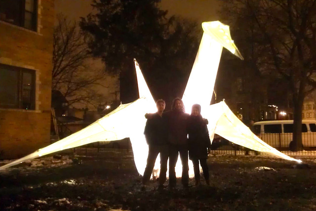<p>Eric Stahl-David, left, Yly and Sima Cunningham pose in front of the giant &quot;origami&quot; crane they built.</p>