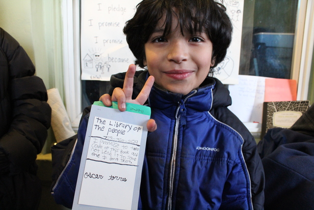 <p>Joaquin, nine, holds up an example library card for The People&rsquo;s Library, a &ldquo;micro-library&rdquo; started by Rachel Perveiler on her back porch.</p>