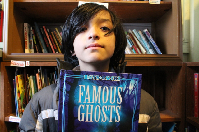 <p>Jos&eacute;, 10, holds up a book on ghosts. Behind him is a bookcase of books from The People&rsquo;s Library, which teacher Rachel Perveiler started on the back porch of her Little Village apartment.</p>