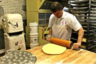 Quigley helps roll dough that will eventually become bismark doughnuts.