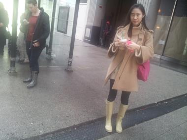 "Sarah Yoo, 21, a student, waits for Michigan Avenue bus dressed for weather Tuesday. She said she was wearing Hunter brand rain boots for first time this season and ""didn't expect to be wearing them today."""
