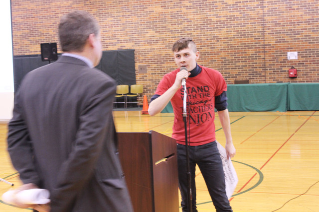 <p>Ryan Polker grabs the microphone during a public meeting about school closures. CPS officials had difficulty getting through their prepared presentation because of outbursts from the crowd.</p>