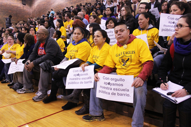 <p>A parent from Gale Elementary holds a sign in support of his school.</p>