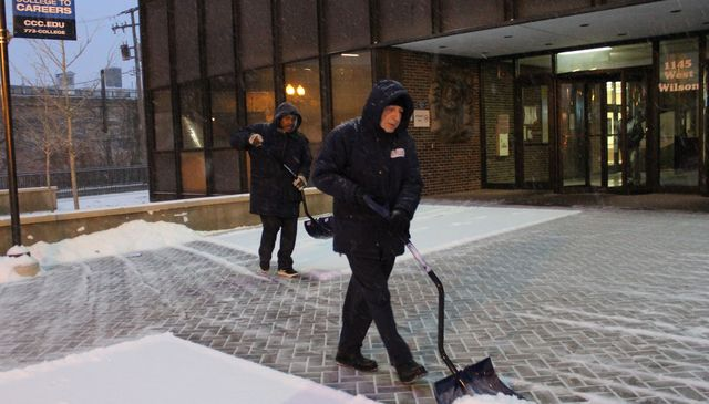 <p>Johnnie Holly (l.) and Arkady Tsilker shovel snow outside Truman College on West Wilson Avenue early Friday morning.</p>