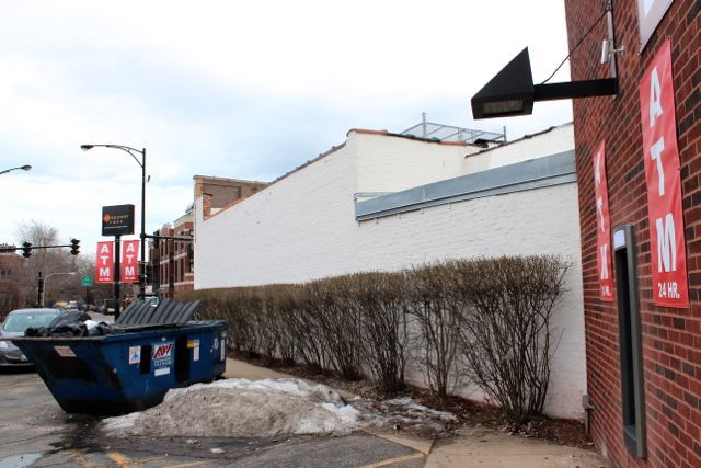 <p>A 24-Hour ATM was installed at 1704 N. Milwaukee Ave. on the southern end of a strip mall, in front of a handicap parking space, obscured by a garbage bin and next to a wall and bush. A security camera is positioned above the machine along with bright lights.</p>