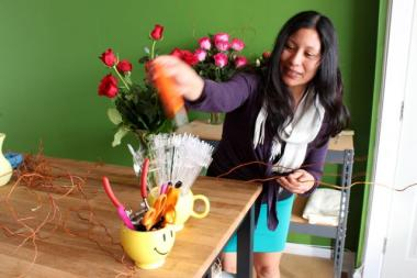 Benitz Ocasio, 32, arranges a bouquet of roses Wednesday, the first day of business for Vased Flowers' new location at 2121 N. Western Ave.