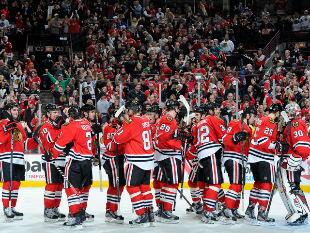 <p>The Blackhawks celebrate after their 2-1 victory over the San Jose Sharks on Friday night at the United Center. The win was the 17th straight game that Chicago had earned at least one point to start the regular season, which set an NHL record.</p>