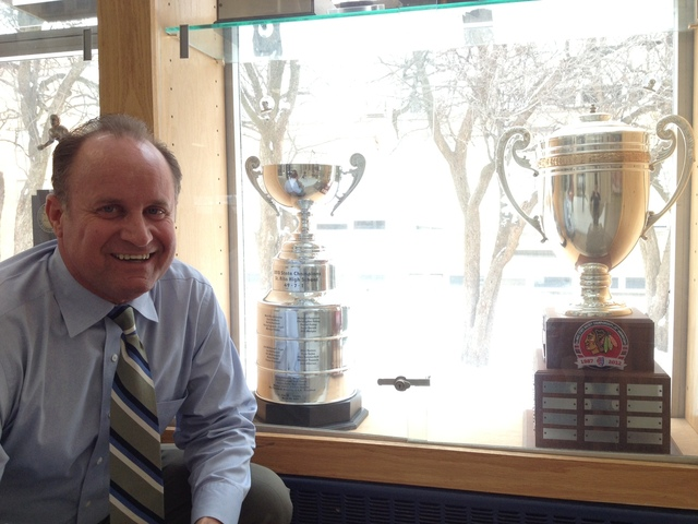 <p>St. Rita hockey coach Craig Ferguson poses in front of the team&#39;s 2012 and 2010 state championship trophies at the school.</p>