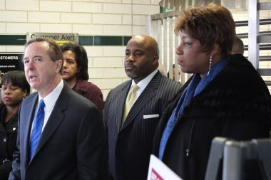 With CTA Chairman Terry Peterson (c.) and Ald. Pat Dowell (r.) looking on, CTA President Forrest Claypool explains the service changes intended to address the Red Line reconstruction project.