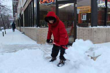 Edna Pak, 65, shovels the sidewalk outside the Happy Wash laundromat on West Wilson Avenue in Uptown Friday morning.