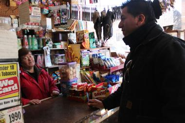 Puerto Rican Cultural Center food coordinator Abel Fernandez talks to bodega owner Angelina Claudio about how the fruit has been selling.