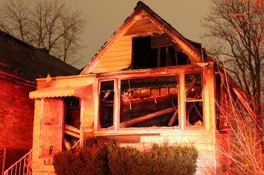 The roof of a burning Auburn Gresham home collapsed on two firefighters early Tuesday, sending them crashing into the basement. Both were taken to a local hospital in good condition.
