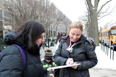 Rachel Lessem, left, assists Christina Nelson with signing a petition against 'High Stakes Standardized Tests' in front of Pritzker School in Wicker Park Wednesday.   Both women are parents of Pritzker students.