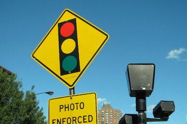 A sign warns driver of red light camera enforcement at Foster and Broadway.
