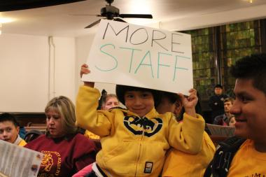 A girl holds a sign declaring her school's need for more staff at Monday night's CPS school closings meeting.