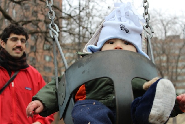 <p>Sieji Ginsburg, nearly a year old, is pushed on a swing in Telscer Park by his father, Jonas Ginsburg.</p>