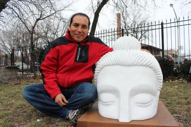 "Artist and sculptor Alfonso ""Piloto"" Nieves poses with the Ten Thousand Ripples Buddha head at the Gads Hill Center (1919 W. Cullerton St.). Nieves and his students are collaborating on a three-dimensional response piece that would sit facing the Buddha head."