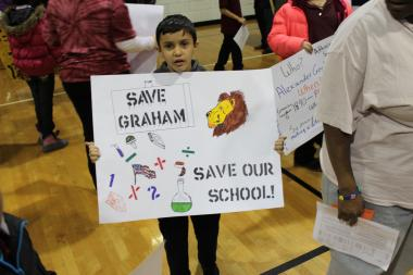A young supporter of Graham Elementary school holds a sign at Thursday's CPS forum on potential closings in the Pershing Network.