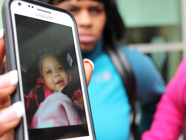 <p>Family holds up a photo of 6-month-old Jonylah Watkins.</p>