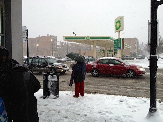 <p>People wait for a bus at 35th Street and King Drive during a snowstorm Tuesday.</p>