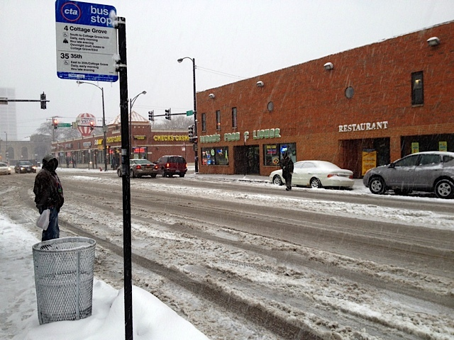 <p>A man waits for a bus at 35th Street and Indiana Avenue during a snow storm Tuesday.</p>