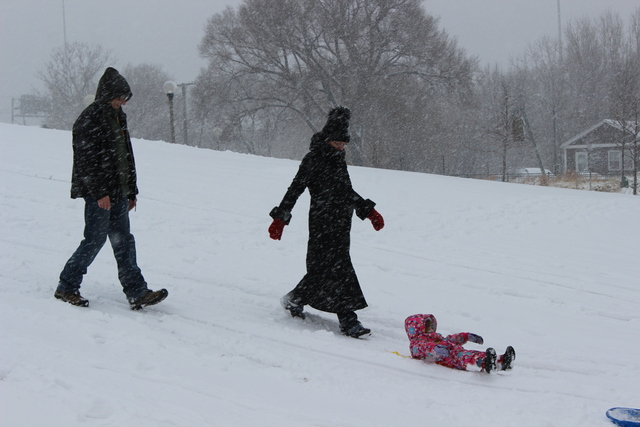 <p>A married couple take their two-year-old daughter sledding for the first time Tuesday.</p>