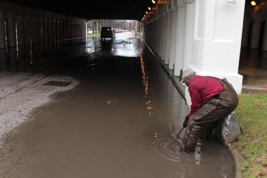 Micah Downs, a maintenance worker at the University of Chicago, tries to unclog a storm drain on East 60th Street. The eastbound lane of the Midway Plaisance was closed to traffic all day Thursday because of flooding.