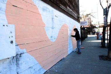 "Street artist ""Milk"" works on a new piece on the wall of The Violet Hour Wednesday."