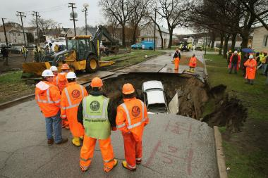 A sinkhole claimed three cars and injured one person on the Southeast Side Thursday.