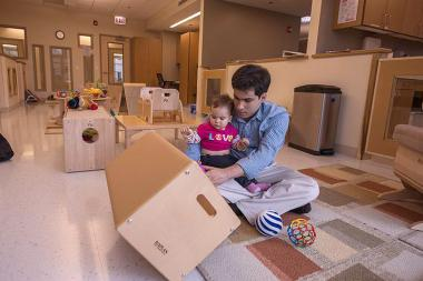 Professor Alfredo César Melo plays with his daughter, Bianca, during a visit to the new University of Chicago child care center. The university plans to open a second day care center in the fall.