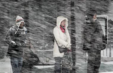 Pedestrians wait to cross the street on March 5, 2013 in Chicago. The National Weather Service said the New Year's Eve snowfall to continue in the new year.