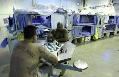 Two inmates in California play chess in 2007 in a gym modified to house prisoners.