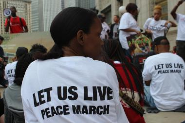 "Hundreds joined Rev. Corey Brooks Saturday afternoon to march up North Michigan Avenue and stage a ""silent sit-in"" to help spotlight young people who are disproportionatley affected by violence in Chicago."