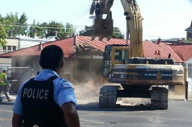 A police officer watches the demolition of the Whittier Elementary fieldhouse on Saturday, Aug. 17.